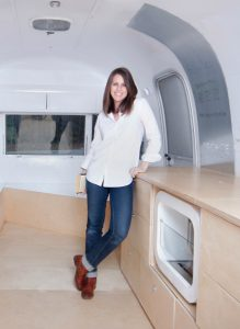 Lacey Haslam stands inside the Archive of Creative Culture's Airstream Argosy